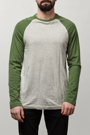 partial view of man in basic raglan sleeve baseball shirt with copy space isolated on grey Stock Photo