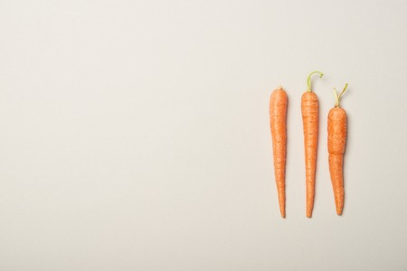 Top view of fresh carrots on grey background