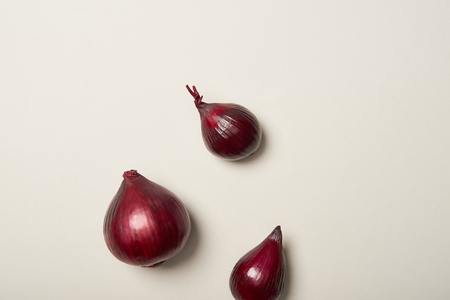 Top view of three red onions on grey background