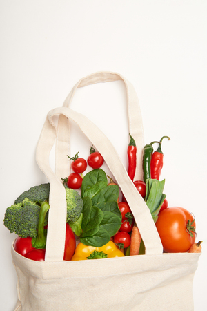 Studio shot of eco bag with vegetables on white background