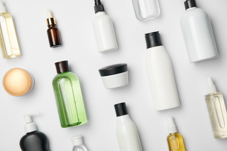 Top view of various cosmetic bottles and containers on white background 스톡 콘텐츠