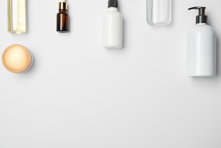 Top view of different cosmetic bottles on white background with copy space