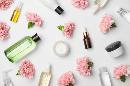 Draufsicht auf verschiedene Kosmetikbehälter und rosa Nelkenblüten auf weißem Hintergrund