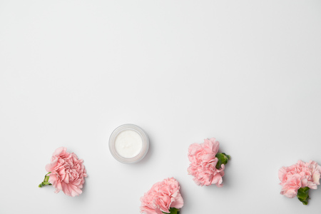 Top view of pink carnations flowers and cream container on white background Imagens