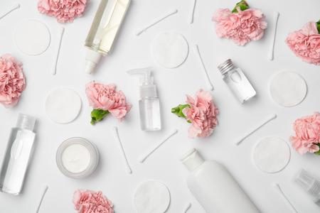 Draufsicht auf verschiedene Kosmetikflaschen, Nelkenblumen, Wattestäbchen und Kosmetikpads auf weißem Hintergrund