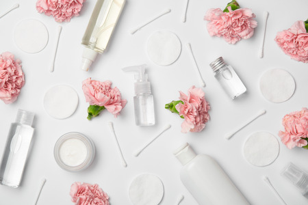 Top view of different cosmetic bottles, carnations flowers, cotton sticks and cosmetic pads on white background 스톡 콘텐츠