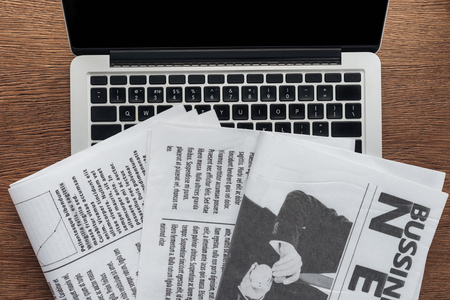 Top view of newspapers and laptop on wooden tabletop 版權商用圖片 - 116388000