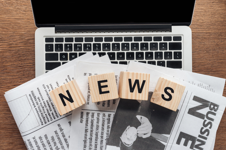 Top view of wooden cubes with word news and newspapers on laptop on wooden tabletop