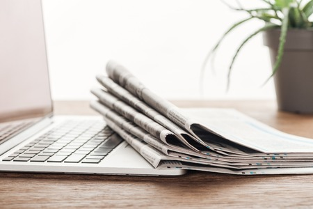 Laptop, plant and stack of newspapers on wooden tabletop 版權商用圖片 - 116388011