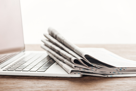 Laptop and stack of newspapers on wooden tabletop