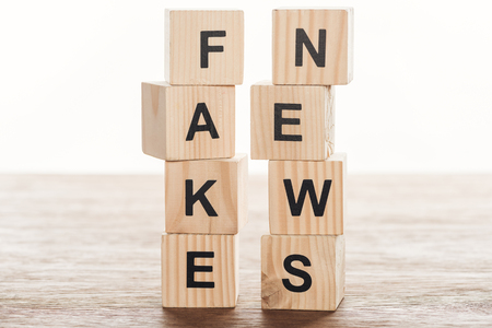 Wooden cubes with words fake news on wooden tabletop