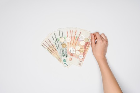 cropped view of woman hand and Russian rubles with coins on grey background