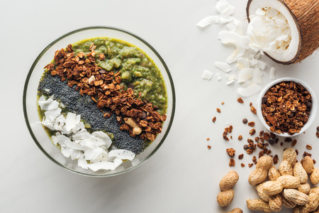 Top view of fresh green smoothie bowl with ingredients on white background Stock Photo