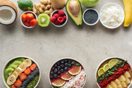 Top view of smoothie bowls with ingredients on grey background Stock Photo
