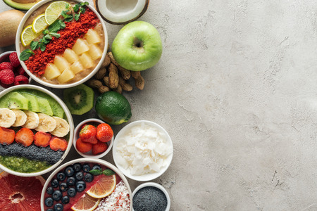 Top view of healthy smoothie bowls with ingredients on grey background Stock Photo