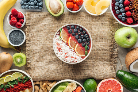 Top view of smoothie bowls and frame made of fresh ingredients on sackcloth