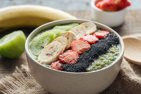 selective focus of smoothie bowl with bananas, strawberries and poppy seeds on sackcloth