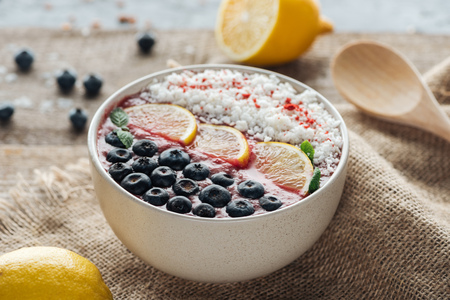 selective focus of smoothie bowl with fresh fruits on sackcloth Stock Photo