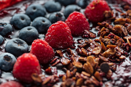Selective focus of blueberries, raspberries and granola in smoothie bowl Stok Fotoğraf