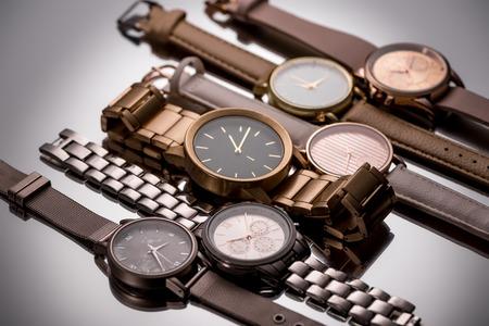 Relojes de pulsera de lujo con manecillas de reloj sobre fondo gris