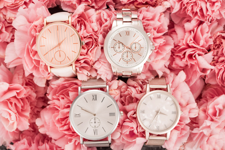 top view of wristwatches lying on blooming pink flowers Stock Photo