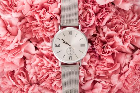 top view of luxury wristwatch lying on blooming flowers