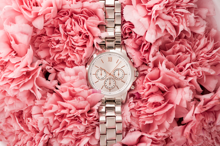top view of elegant wristwatch lying on blooming flowers Stock Photo