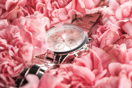 elegant wristwatch lying on blooming pink flowers