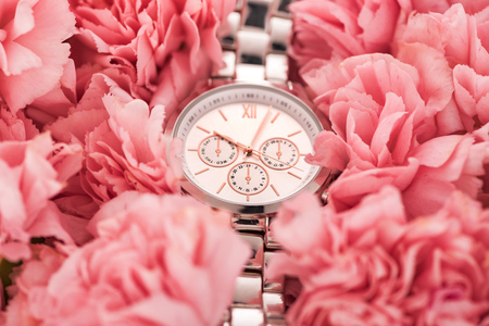 elegant wristwatch lying on blooming pink carnations