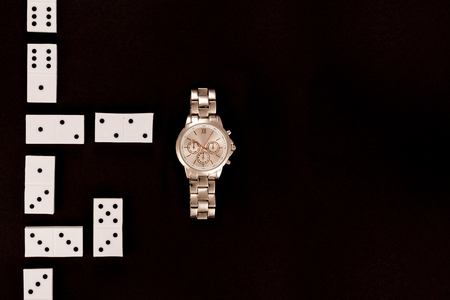 top view of luxury wristwatch lying near dominoes isolated on black Stock Photo - 116464844