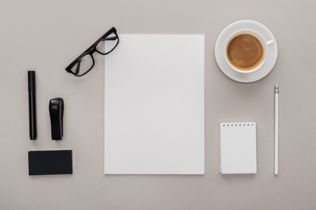 top view of black and white stationery at workplace with cup of coffee on grey background
