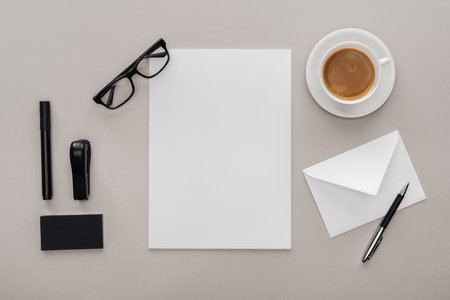 top view of office supplies and cup of coffee on grey background
