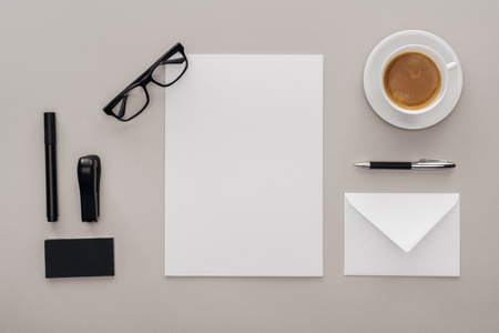 top view of office supplies at workplace with cup of coffee on grey background