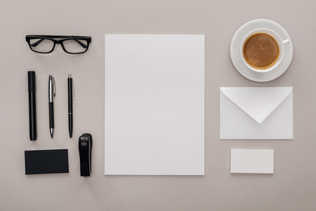 flat lay with black glasses, stationery and white empty cards at workplace with cup of coffee on grey background