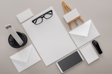 flat lay with blank cards, glasses, smartphone and stationery on grey background