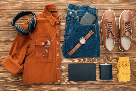 Flat lay with headphones, hip flask and male clothes on wooden background
