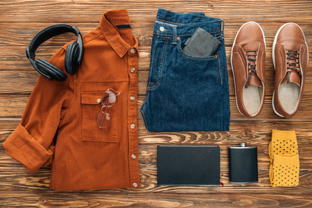 Flat lay with headphones, hip flask and clothes on wooden background Stok Fotoğraf