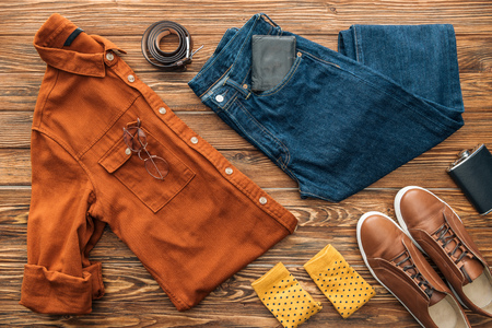 Flat lay with shirt, jeans and shoes with accessories on wooden background