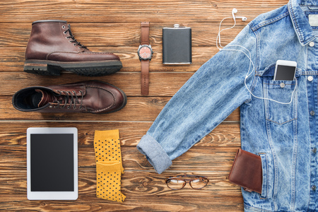 Flat lay of boots, denim jacket and digital devices on wooden background