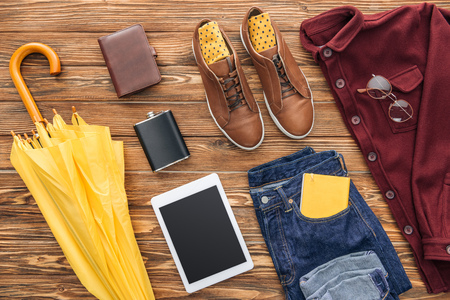 Flat lay with mens clothing, digital tablet and yellow umbrella on wooden background