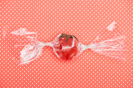 top view of red fresh tomato in transparent candy shaped wrapping on red dotted background