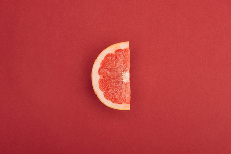 top view of half slice of fresh ripe juicy grapefruit red background Foto de archivo