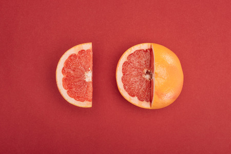 top view of grapefruit slice and partially cut grapefruit on red background