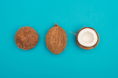 top view of whole coconut and coconut halves on blue background 版權商用圖片