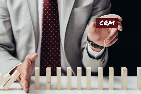 partial view of businessman holding brick with crm word and preventing wooden blocks from falling