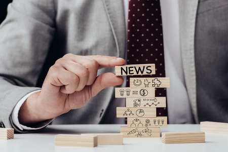 cropped view of man holding brick with word news over wooden blocks with icons