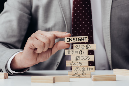 cropped view of man holding brick with word insight over wooden blocks with icons Stock fotó