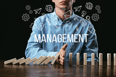 cropped view of man preventing wooden blocks from falling with word management and icons on foreground Banco de Imagens