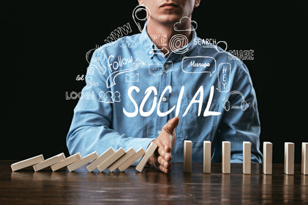 cropped view of man preventing wooden blocks from falling with word social and icons on foreground