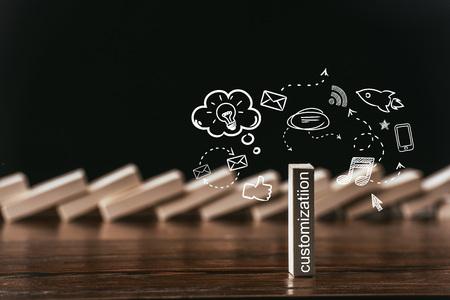 selectieve focus van houten baksteen met woord 'maatwerk' en pictogrammen geïsoleerd op zwart